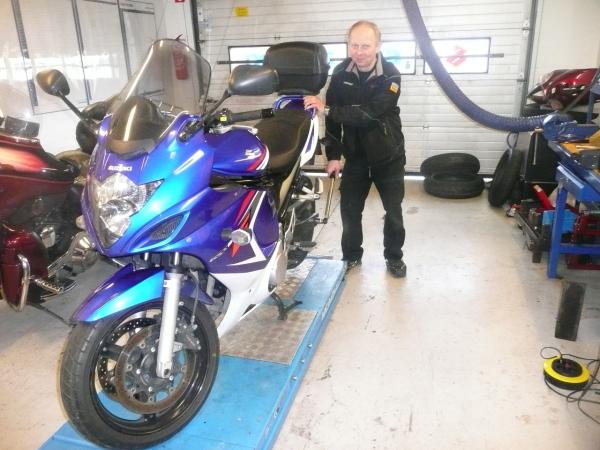 Motorcycle mechanic doing maintenance on Suzuki